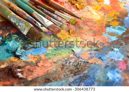 Artist paintbrushes over palette with oil colors - stock photo