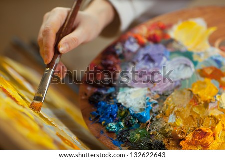 artist paints a picture of oil paint brush in hand with palette closeup - stock photo
