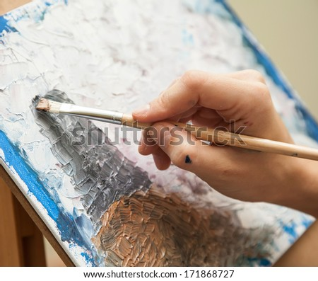 artist paints oil painting on canvas - stock photo
