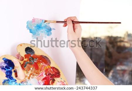 Artist paints picture close-up - stock photo