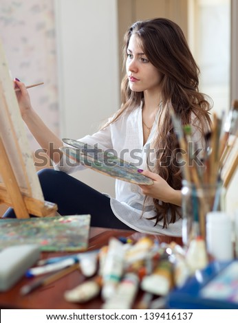 artist paints picture on canvas with oil paints in her workshop - stock photo