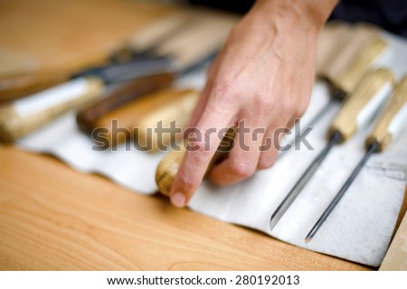 Artist picking cheesel for wood carving,shallow depth of field - stock photo