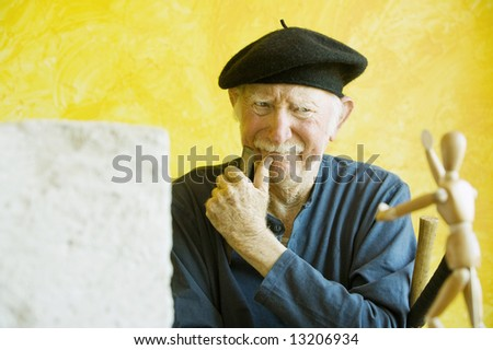 Artist ponders a wooden figure model - stock photo