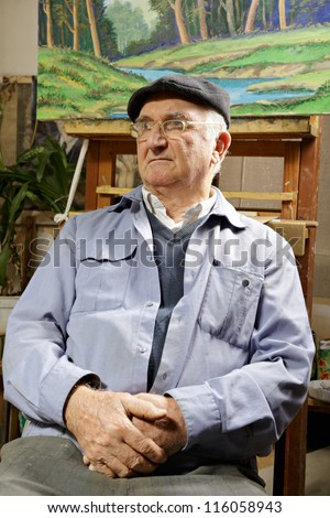 Artist sitting in chair under his painting looking sideways - stock photo