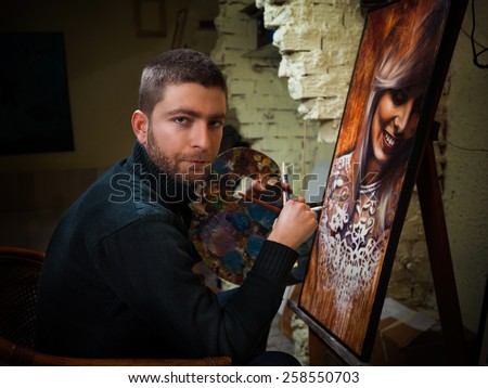 Artist sitting in his studio holding cigarette and paintbrushes working on oil painting portrait of beautiful young woman. - stock photo