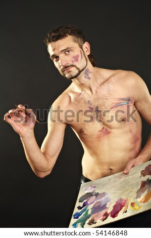 Artist with brush and palette in action - stock photo