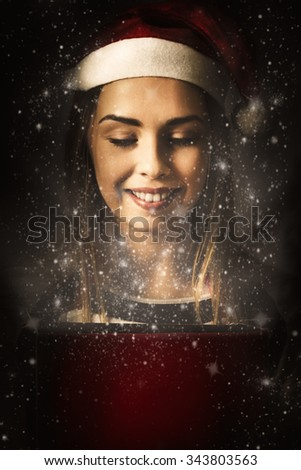 Artistic abstract photo on a beautiful girl opening a wondrous red christmas gift box with sparkles of miraculous light and glittering happiness. Magic of christmas - stock photo