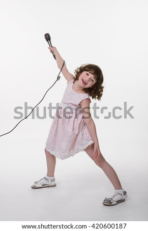 Artistic beauty is very naughty. Young caucasian female straddled her legs and rised her hand with the microphone in it. Cute clothes for little girls. - stock photo