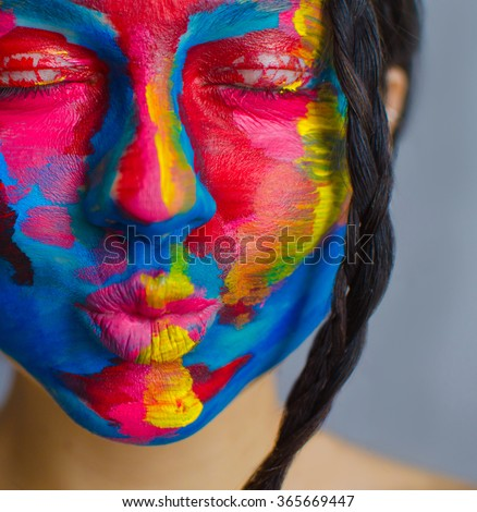 Artistic colorful portrait of a young beautiful model  with face covered with thick paint - stock photo