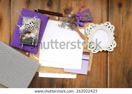 Artistic composition with lavender seeds and flowers next to a purple diary notepad placed next to a rounded photo frame and notebooks over white and brown sheets of paper and weathered, vintage wood - stock photo