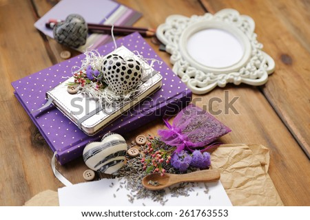 Artistic composition with lavender seeds and flowers next to a purple diary notepad under a white address book and a heart next to a white photo frame, wooden spoon and a sheet of paper on brown wood - stock photo