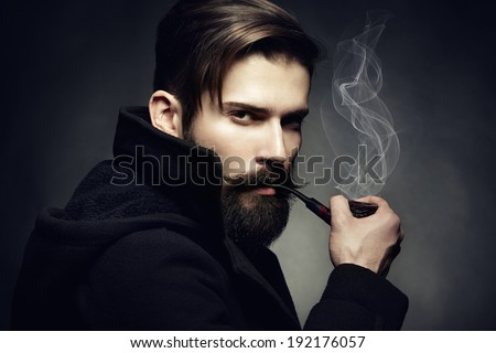 Artistic dark portrait of the young beautiful man. The young man smokes a tube. Close up - stock photo