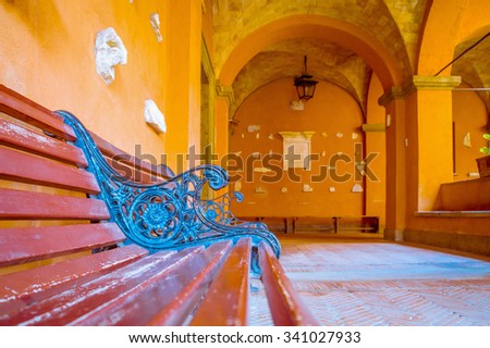 Artistic edit of a wooden bench ornament in blue tones, in contrast with red and orange surrounding walls - stock photo