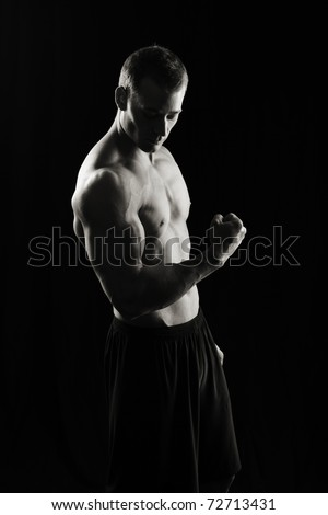 Artistic fitness man on black - stock photo