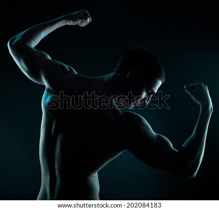 Artistic Fitness on a black background, Low key portrait of young bodybuilder posing and showing muscles. Noise added in post production, - stock photo