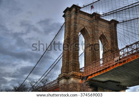 Artistic HDR image of the Brooklyn Bridge on a cloudy day (close up upward view image) - stock photo