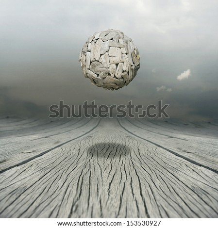 Artistic metaphysical background representing a ball sculpture floating in the air above a wooden floor with the sky on the background - stock photo
