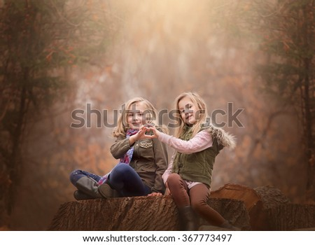artistic moody outdoor portrait of two blond girls sitting on a log of tree in a woods, great artistic expression of friendship - stock photo