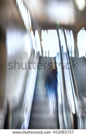 Artistic motion blur of blue woman in escalator. - stock photo