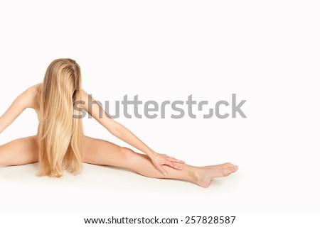 Artistic nude of an attractive female gymnast with long blond hair working out in front of white background, her private parts are not visible, photo with copy space on the right side of the image - stock photo