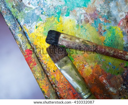 Artistic paintbrushes  on an old wooden palette - stock photo