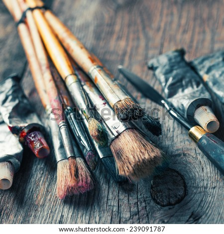Artistic paintbrushes, tubes of oil paint, palette knife on old wooden desk. Vintage stylized. - stock photo
