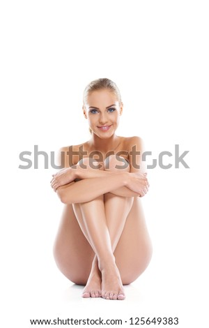 Artistic portrait of a beautiful woman posing implied nude sitting on the floor with her legs drawn up in front of her, studio portrait on white - stock photo