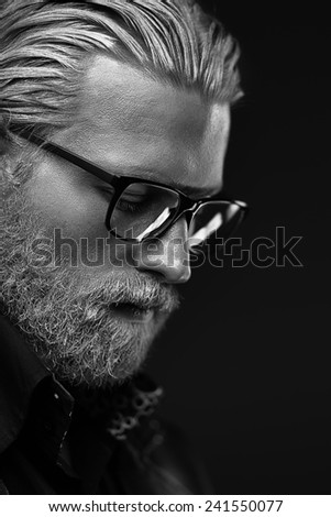 Artistic portrait of gray haired man on black background - stock photo