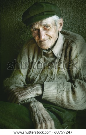 Artistic portrait of old senior man with wrinkled hands - stock photo
