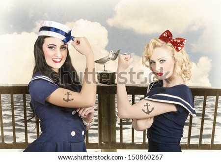 Artistic portrait of two sexy sailor pin up girls with anchor tattoos flexing muscles on a vintage pier promenade when competing in strength and conditioning exercises. Vintage pinup style - stock photo