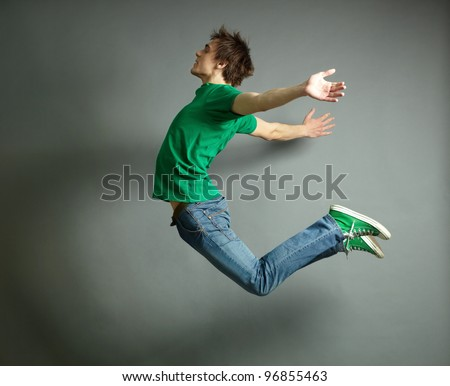 Artistic shot of a guy jumping high and posing meanwhile - stock photo