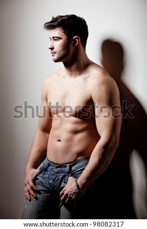 artistic shot of a handsome young man propped on the wall - stock photo