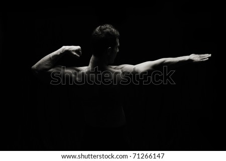 Artistic strong man on black background, low key lighting style - stock photo