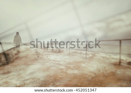 Artistic surreal double exposure of lonely person walking on pier.  - stock photo