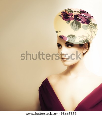 Artistic toned portrait of a woman in high fashion wearing a plunging neckline and floral pillbox hat - stock photo