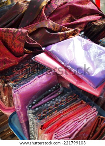artistic variety shade tone colors ornaments patterns of thai silk textiles with traditional cultural decoration ornaments design by village people for sale in a street market in KHONKAEN, THAILAND  - stock photo