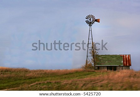 Artistic view of old barn and windmill with wind blown field - stock photo