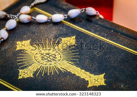 Artistic vintage edit composition of a prayer book or Bible with golden cross on its cover and an old white rosary on top of it - stock photo