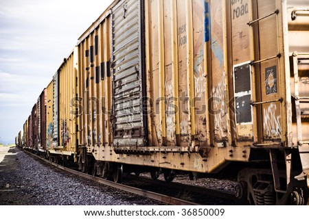 Artistic yellow and brown train cars and tracks - stock photo