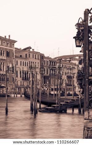 Artistically toned canal scene in Venice with a gondola and beautiful old buildings and architecture lining the waterway - stock photo