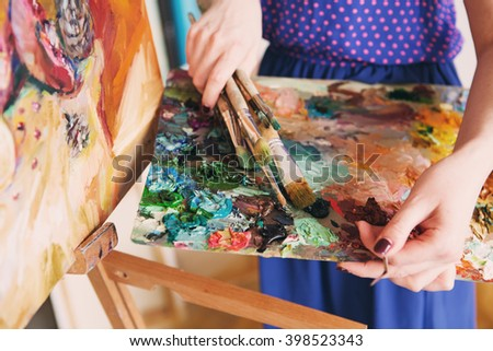 artists brushes and oil paints on wooden palette. palette with paintbrush and palette-knife in artists hands. The girl artist holding a palette with oil paints - stock photo
