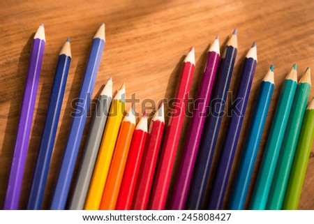 Artists colored pencil on a rustic wooden table. - stock photo