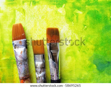Artists paint brushes in studio in front of abstract background - stock photo