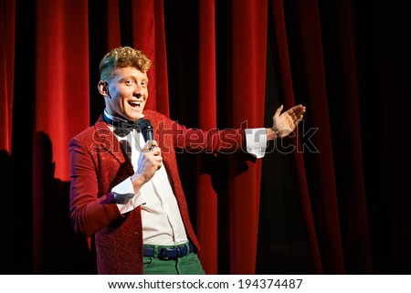 Arts and entertainment in theatre with funny man working as anchorman, standing against red curtains with microphone - stock photo