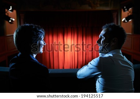 Arts and entertainment in theatre, with man and woman looking at stage with red curtains - stock photo
