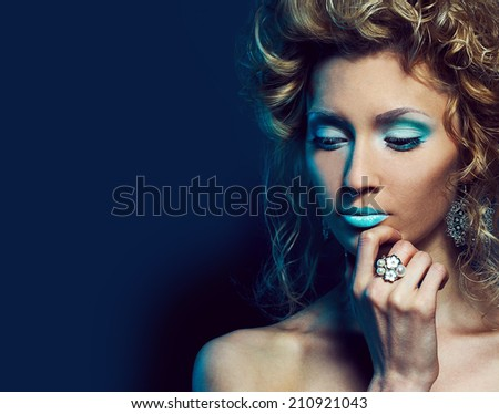Arty portrait of a beautiful woman with snow make-up with luxurious accessories. Close up - stock photo