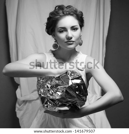 Arty portrait of a fashionable queen-like model holding silver foil sphere over white curtain background. Black and white (monochrome) studio shot - stock photo