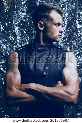 Arty portrait of muscular young and handsome man with muscular hands and trendy haircut posing over sparkling background. Studio shot - stock photo