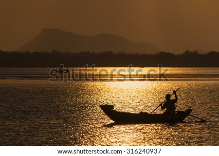 Arugam bay lagoon, Sri Lanka - July 20, 2014: Traditional fisherman boating in dugout canoe in Arugam bay lagoon in sunset time, Sri Lanka.  - stock photo