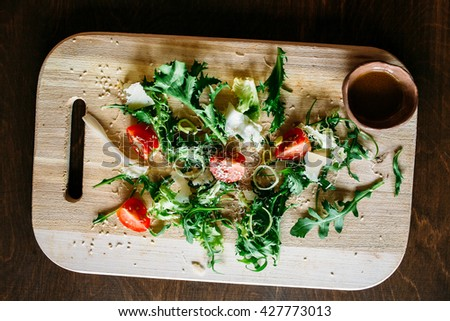 Arugula and tomato, salad on a wooden board,  arugula salad with tomatoes and parmesan, salad of arugula, salad on a brown background, salad with sesame seeds - stock photo